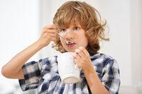 Junge löffelt eine Tasse Kakao
