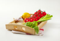 Wooden serving tray wit fresh vegetables and fruit
