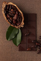 Chocolate, cocoa beans and  leaves on dark background.