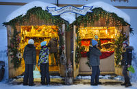 romantic christmas market in Bavaria with illuminated wooden shops in snow