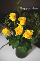 A very beautiful bouquet of yellow roses stands in a green vase and two glasses of red wine. Romantic evening. Lettering happy day.