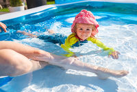 2 years old child in swimming pool on summer day with mother.