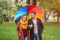 A beautiful young couple is walking in the park under a rainbow colored umbrella. A beautiful girl walks through the autumn park arm in arm with a guy in rainy weather