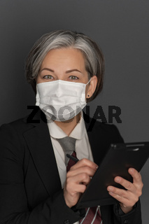 Caucasian grey haired businesswoman in protective mask work using digital tablet gadget looking at camera isolated on grey background. Studio shot