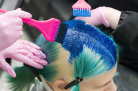 Two hairdressers using pink brush while applying blue paint to female with emerald hair color during process of dyeing hair in unique lapis lazuli color