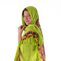 Smiling young girl with a green headscarf looks into the camera isolated on white