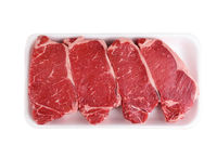 Four Boneless Beef Loin New York Steaks in a styrofoam tray isolated on white.