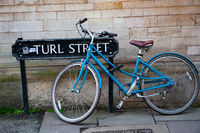 A blue bicycle locked on Turl Street, Oxford, England