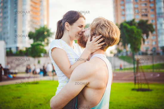 Love, fun, spott and people. Portrait of a happy young couple smiling, hugging and having fun while training. Happy athletic couple talking and piggybacking on park. Concept sport and love