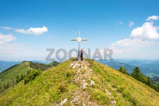 Wanderer am Gipfelkreuz des Almkogels in Oberösterreich