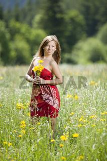 Junge Frau auf einer Wiese mit Blumen