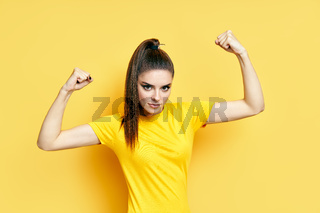 Powerful confident young woman showing arms muscles on yellow background