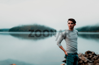 Portrait of young male model on a rainy day with a beautiful lake in the background