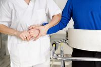 female nurse caregiver, holding patient hand, support disabled patient sit on wheelchair at hospital, young doctor carer help paralyzed patient.