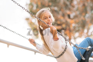 Happy Girl, smiling On Swing In Park at sunset.
