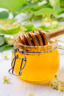 Jar of lime honey with a wooden dipper.