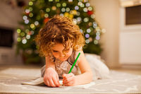 Little curly girl writing letter on the floor