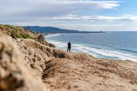 Man with panoramic view of ocean with distant pier and parachuter in San Diego