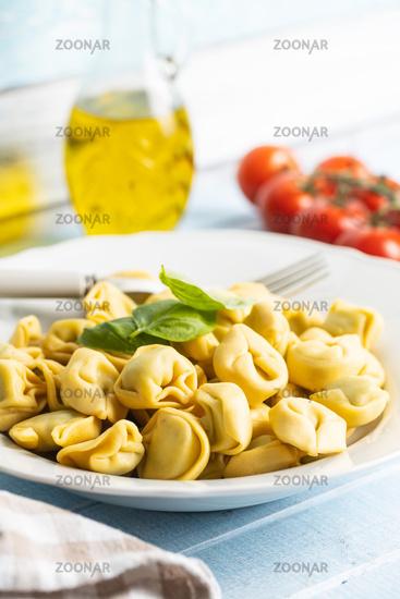 Tortellini pasta. Italian stuffed pasta with basil leaves.