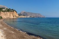 Tranquil stone beach with view on rocky cliffs, Altea, Costa Blanca, Spain