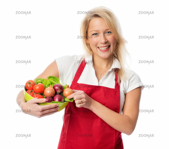 woman with apron holding a bowl of vegetables