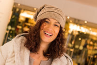 portrait of a smiling young woman with a hat and background of a shop window
