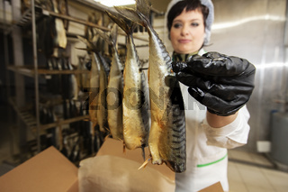 September 18, 2020. Belarus, Gamil. Fish factory.Fish factory worker with smoked fish. Fish industry.