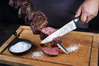 Traditional barbecue dry aged wagyu Brazilian picanha from the sirloin cap of rump beef sliced by a chef directly from the skewer as close-up on a wooden cutting board
