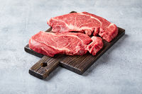 Two Fresh Raw meat Prime Black Angus Beef Steaks, Rib Eye, Denver, on wooden cutting board