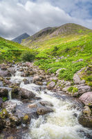 Winding mountain stream in Cronins Yard, a green valley with Carrauntoohil in a distance