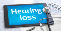 The word Hearing loss on the display of a tablet