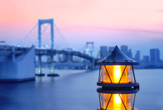 Lantern of the Rainbow Bridge on the bay of Odaiba with illuminations in sunset sky.