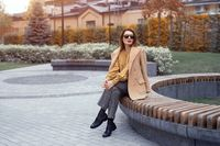 Beautiful young autumn french woman in beige coat and sunglasses sits on a flowerbed bench waiting for her date or girlfriends. Soft warm toned photo