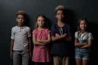 Four adorable cute multinational children school age girls boys looking at camera pose lean at dark grey wall studio background. Alpha generation beautiful different ethnicity kids portrait concept
