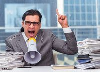 Angry businessman with loudspeaker in the office