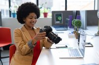 Smiling mixed race businesswoman sitting at desk using camera in creative office
