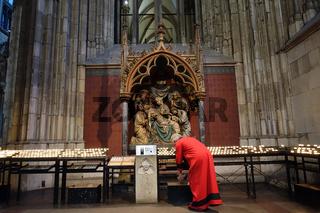 Opferkerzen und Opferstock vor einer Pietà im Kölner Dom, davor ein Kirchenschweizer in roter Robe