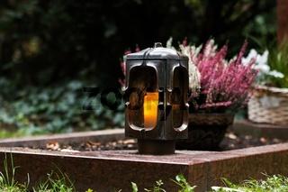 Grablaterne aus Metall mit brennender Kerze