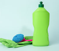 green rubber gloves for cleanin and cleaning fluid in a plastic bottle on a blue background