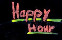 Happy hour written on black chalkboard with chalk