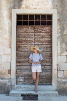 Beautiful young female tourist woman standing in front of vinatage wooden door and textured stone wall at old Mediterranean town, smiling, holding, smart phone to network on vacationes