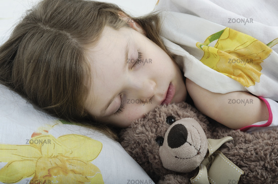 Little girl sleeping in her bed with teddy bear