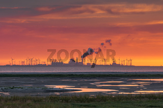 Sonnenuntergang am Watt mit Windturbinen und Industriegebäude im Hintergrund