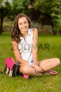 Cheerful student girl with briefcase sitting grass