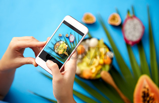 hands taking photo of exotic fruits on smartphone