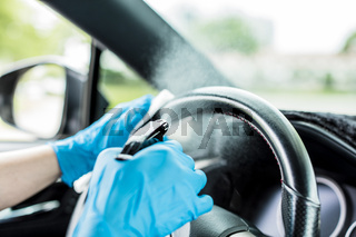 Hands with blue gloves then sprinkling disinfectant and cleaning the car