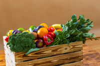 Wooden box of fresh fruit and vegetable on brown table.