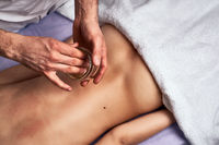 Male masseur doing massage using special aromatic oil on beautiful naked woman body in the spa salon. Beauty treatment concept.
