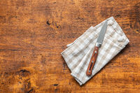 Kitchen knife on checkered napkin.