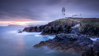 Twilight yields to dawn, sunrise at Fanad Head Lighthouse with blurred water of Atlantic Ocean